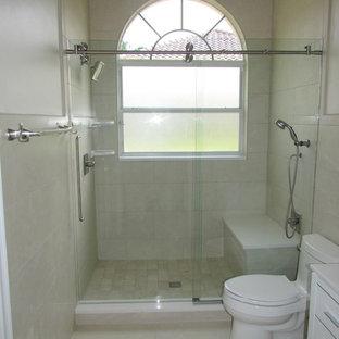 На фото: ванная комната среднего размера в стиле модернизм с фасадами с декоративным кантом, белыми фасадами, душем в нише, унитазом-моноблоком, бежевой плиткой, плиткой из известняка, бежевыми стенами, полом из керамогранита и душевой кабиной с