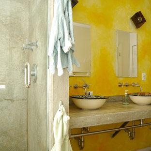 Foto de cuarto de baño principal, bohemio, de tamaño medio, con lavabo sobreencimera, encimera de cemento, baldosas y/o azulejos de terracota, paredes amarillas y suelo de cemento