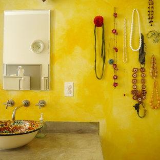 Foto de cuarto de baño principal, ecléctico, de tamaño medio, con lavabo sobreencimera, encimera de cemento, jacuzzi, paredes amarillas y suelo de cemento