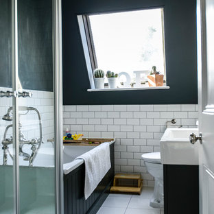 Photo of a classic bathroom in London with an integrated sink, black cabinets, a built-in bath and black walls.