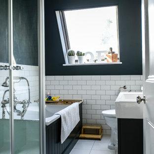 ロンドンのトランジショナルスタイルのおしゃれな浴室 (一体型シンク、黒いキャビネット、ドロップイン型浴槽、黒い壁) の写真