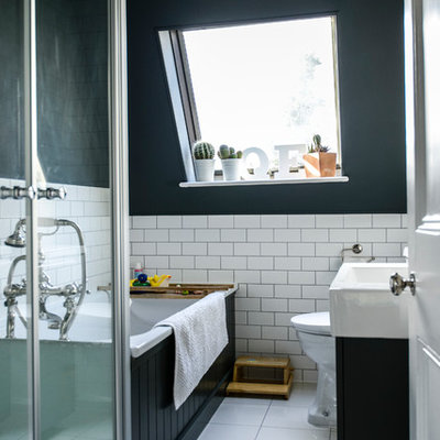 Transitional drop-in bathtub photo in London with an integrated sink, black cabinets and black walls