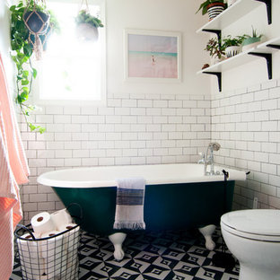 Inspiration for an eclectic master subway tile and black and white tile ceramic floor claw-foot bathtub remodel in Los Angeles with white walls