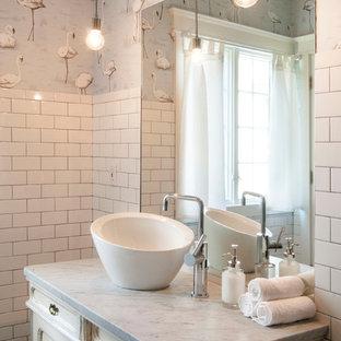 Modelo de cuarto de baño ecléctico, de tamaño medio, con lavabo sobreencimera, armarios tipo mueble, puertas de armario con efecto envejecido, encimera de mármol, baldosas y/o azulejos blancos, baldosas y/o azulejos de cemento, paredes multicolor y suelo de baldosas de cerámica