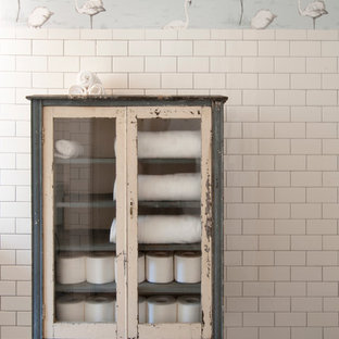 Inspiration for a mid-sized eclectic white tile and subway tile ceramic floor alcove shower remodel in Cleveland with a vessel sink, distressed cabinets, marble countertops, white walls and glass-front cabinets