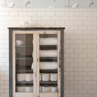 Imagen de cuarto de baño ecléctico, de tamaño medio, con lavabo sobreencimera, puertas de armario con efecto envejecido, encimera de mármol, ducha empotrada, baldosas y/o azulejos blancos, baldosas y/o azulejos de cemento, paredes blancas, suelo de baldosas de cerámica y armarios tipo vitrina