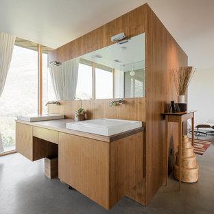 Imagen de cuarto de baño contemporáneo con armarios con paneles lisos, puertas de armario de madera oscura, paredes blancas, suelo de cemento y lavabo sobreencimera