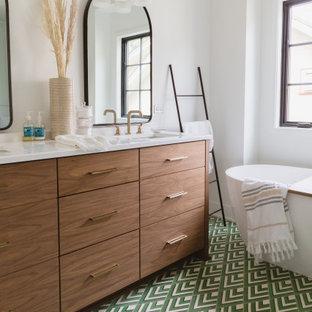 シカゴの北欧スタイルのおしゃれなマスターバスルーム (フラットパネル扉のキャビネット、中間色木目調キャビネット、置き型浴槽、白い壁、マルチカラーの床、白い洗面カウンター、洗面台2つ、造り付け洗面台、三角天井) の写真
