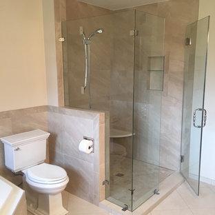Immagine di una stanza da bagno padronale tradizionale di medie dimensioni con vasca da incasso, doccia ad angolo, WC a due pezzi, piastrelle grigie, piastrelle in ardesia, pareti beige, pavimento con piastrelle in ceramica, pavimento beige e porta doccia a battente