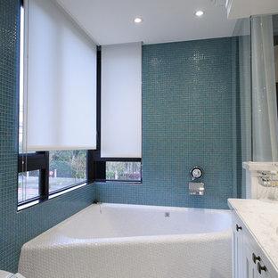Idée de décoration pour une salle de bain design avec une baignoire d'angle et carrelage en mosaïque.