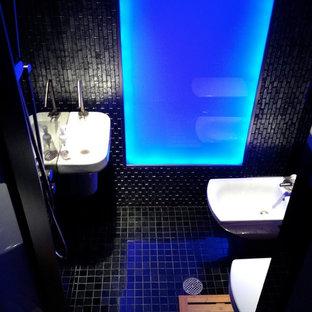 Ejemplo de cuarto de baño con ducha, moderno, pequeño, con lavabo suspendido, combinación de ducha y bañera, sanitario de pared, baldosas y/o azulejos negros, baldosas y/o azulejos de vidrio y paredes negras