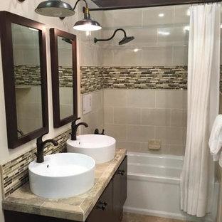 Idéer för ett litet modernt badrum med dusch, med släta luckor, svarta skåp, ett badkar i en alkov, en dusch/badkar-kombination, flerfärgad kakel, glaskakel, beige väggar, kalkstensgolv, ett fristående handfat och kaklad bänkskiva