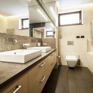 他の地域の広いトランジショナルスタイルのおしゃれなマスターバスルーム (フラットパネル扉のキャビネット、茶色いキャビネット、ドロップイン型浴槽、一体型トイレ、茶色いタイル、ベージュの壁、一体型シンク、茶色い床、ベージュのカウンター、セラミックタイル、セラミックタイルの床、御影石の洗面台) の写真