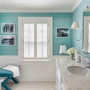 Maritim inredning av ett badrum, med ett undermonterad handfat, luckor med infälld panel, vita skåp, blå väggar och mosaikgolv