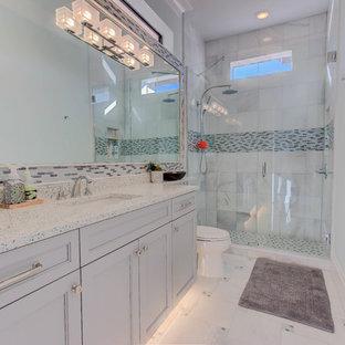Foto de cuarto de baño contemporáneo, de tamaño medio, con armarios estilo shaker, puertas de armario grises, ducha abierta, sanitario de dos piezas, baldosas y/o azulejos blancos, baldosas y/o azulejos de porcelana, paredes azules, suelo de baldosas de porcelana, lavabo bajoencimera, encimera de vidrio reciclado, suelo blanco y ducha con puerta con bisagras