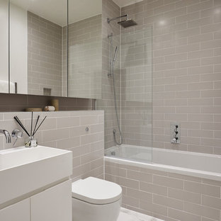 This is an example of a contemporary bathroom in London with flat-panel cabinets, white cabinets, an alcove bath, a shower/bath combination, grey tiles, metro tiles, white floors, an open shower and a console sink.