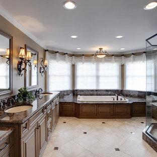 Immagine di una stanza da bagno classica con lavabo sottopiano, ante con bugna sagomata, ante in legno scuro, vasca da incasso, doccia alcova e piastrelle beige
