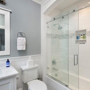 Idee per una grande stanza da bagno con doccia tradizionale con ante con riquadro incassato, ante bianche, lavabo sottopiano, top in marmo, vasca ad alcova, vasca/doccia, piastrelle a mosaico, pareti grigie, pavimento in marmo e WC a due pezzi