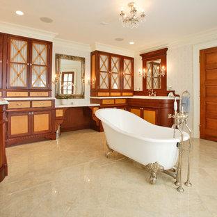 Foto di una stanza da bagno vittoriana con ante di vetro, ante in legno scuro, vasca con piedi a zampa di leone e piastrelle beige