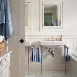 Immagine di una stanza da bagno padronale tradizionale di medie dimensioni con lavabo a consolle, vasca da incasso, WC a due pezzi, piastrelle bianche, pareti bianche e pavimento in marmo