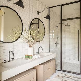 Landhausstil Duschbad mit verzierten Schränken, hellen Holzschränken, bodengleicher Dusche, weißen Fliesen, integriertem Waschbecken, Falttür-Duschabtrennung und beiger Waschtischplatte in New York
