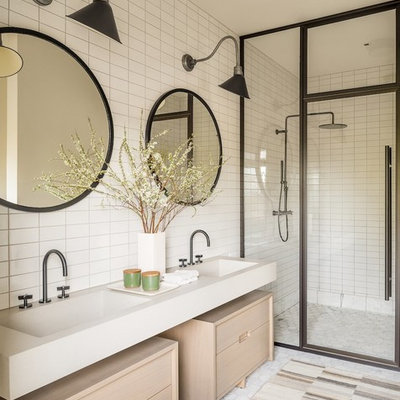 Farmhouse 3/4 white tile walk-in shower photo in New York with furniture-like cabinets, light wood cabinets, an integrated sink, a hinged shower door and beige countertops
