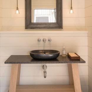 Imagen de cuarto de baño infantil, actual, de tamaño medio, con puertas de armario de madera clara, paredes blancas, suelo de baldosas de porcelana, lavabo sobreencimera, encimera de piedra caliza, suelo marrón y encimeras negras