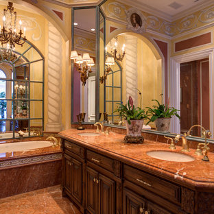 Inspiration for a large mediterranean master porcelain tile and brown tile marble floor doorless shower remodel in New York with raised-panel cabinets, medium tone wood cabinets, a hot tub, a two-piece toilet, red walls, a drop-in sink and marble countertops