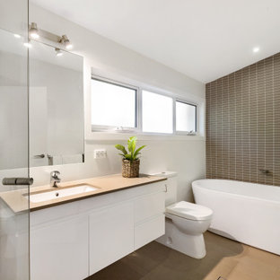 Inspiration for a large contemporary master bathroom in Sydney with a freestanding tub, white walls, porcelain floors, quartzite benchtops, beige floor, beige benchtops, flat-panel cabinets, white cabinets, brown tile and an undermount sink.