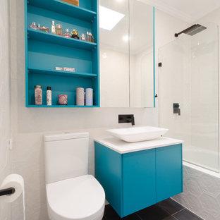 Inspiration för små moderna en-suite badrum, med släta luckor, gröna skåp, ett platsbyggt badkar, en dusch/badkar-kombination, en toalettstol med hel cisternkåpa, grå kakel, keramikplattor, vita väggar, klinkergolv i keramik, ett avlångt handfat och bänkskiva i kvarts