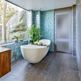 Design ideas for a large contemporary master bathroom in Sydney with a freestanding tub, porcelain tile, porcelain floors, a vessel sink, wood benchtops, grey floor, flat-panel cabinets, dark wood cabinets, blue tile and brown benchtops.