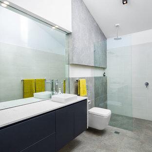 Ispirazione per una grande stanza da bagno con doccia minimal con lavabo a bacinella, ante lisce, ante blu, doccia aperta, WC sospeso, piastrelle grigie e doccia aperta