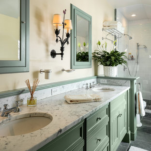 Modelo de cuarto de baño de estilo de casa de campo con armarios con paneles empotrados, puertas de armario verdes, ducha empotrada y paredes beige