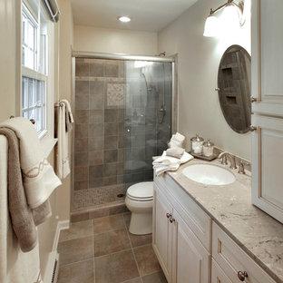 Idéer för mellanstora vintage badrum med dusch, med luckor med upphöjd panel, vita skåp, en toalettstol med separat cisternkåpa, brun kakel, porslinskakel, beige väggar, en dusch i en alkov, klinkergolv i keramik, ett undermonterad handfat, bänkskiva i kalksten, brunt golv och dusch med skjutdörr
