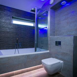 Diseño de cuarto de baño infantil, contemporáneo, de tamaño medio, con bañera encastrada, combinación de ducha y bañera, sanitario de pared, baldosas y/o azulejos grises, paredes grises, suelo de baldosas de cerámica, baldosas y/o azulejos de cerámica, lavabo suspendido, armarios con paneles lisos y puertas de armario grises