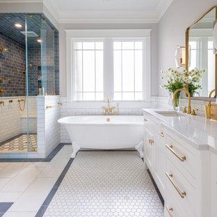 ナッシュビルのトランジショナルスタイルのおしゃれなマスターバスルーム (シェーカースタイル扉のキャビネット、白いキャビネット、猫足バスタブ、コーナー設置型シャワー、グレーのタイル、白いタイル、サブウェイタイル、グレーの壁、モザイクタイル、アンダーカウンター洗面器、白い床、白い洗面カウンター) の写真
