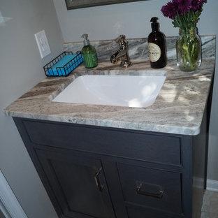 Modelo de cuarto de baño clásico renovado, pequeño, con puertas de armario grises, paredes grises, suelo de linóleo, lavabo bajoencimera y encimera de granito