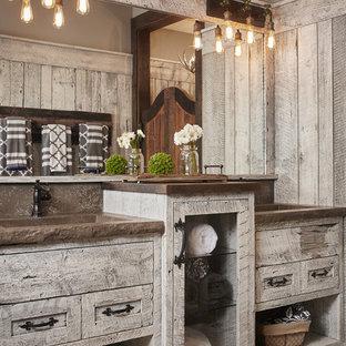 Inredning av ett rustikt badrum, med släta luckor, skåp i slitet trä, grå väggar och ett integrerad handfat