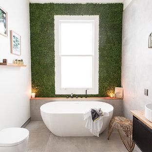 Foto di una stanza da bagno con doccia contemporanea con ante lisce, ante nere, vasca freestanding, WC monopezzo, piastrelle grigie, piastrelle di cemento, pareti bianche, pavimento in cemento, lavabo a bacinella, top in legno, pavimento grigio e top beige