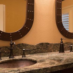 他の地域の小さいラスティックスタイルのおしゃれな浴室 (落し込みパネル扉のキャビネット、濃色木目調キャビネット、アルコーブ型浴槽、シャワー付き浴槽、一体型トイレ、マルチカラーのタイル、オレンジの壁、スレートの床、アンダーカウンター洗面器、御影石の洗面台、ベージュの床、引戸のシャワー、マルチカラーの洗面カウンター) の写真
