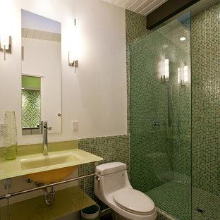 Imagen de cuarto de baño con ducha, vintage, de tamaño medio, con lavabo suspendido, armarios tipo vitrina, encimera de vidrio, ducha abierta, sanitario de una pieza, baldosas y/o azulejos multicolor, paredes blancas y suelo de cemento