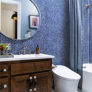 シカゴの中サイズのトランジショナルスタイルのおしゃれなバスルーム (浴槽なし) (レイズドパネル扉のキャビネット、茶色いキャビネット、ダブルシャワー、一体型トイレ、青いタイル、セメントタイル、青い壁、淡色無垢フローリング、オーバーカウンターシンク、珪岩の洗面台、白い床、シャワーカーテン、白い洗面カウンター) の写真