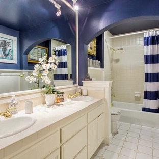 Modelo de cuarto de baño infantil, contemporáneo, de tamaño medio, con armarios estilo shaker, puertas de armario blancas, bañera encastrada, paredes azules, suelo de baldosas de porcelana, lavabo encastrado, encimera de azulejos, suelo gris, ducha con cortina y encimeras beige