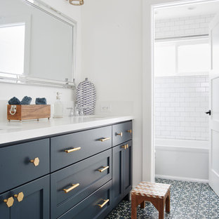Beach style family bathroom in San Francisco with shaker cabinets, blue cabinets, an alcove bath, white tiles, metro tiles, white walls, a submerged sink, multi-coloured floors, a shower/bath combination, a two-piece toilet, cement flooring, engineered stone worktops and a shower curtain.