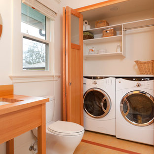Inspiration for a transitional bathroom/laundry room remodel in Portland with an undermount sink, wood countertops, white walls and brown countertops