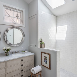 Inspiration for a beach style bathroom in San Francisco with an undermount sink, flat-panel cabinets, light wood cabinets, white tile, subway tile, grey walls and mosaic tile floors.