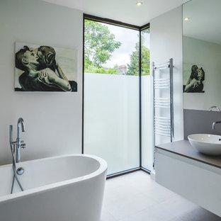 ロンドンの中サイズのコンテンポラリースタイルのおしゃれな子供用バスルーム (フラットパネル扉のキャビネット、白いキャビネット、置き型浴槽、白いタイル、白い壁、テラゾの床、珪岩の洗面台、グレーの床、ブラウンの洗面カウンター) の写真