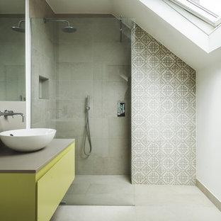 ロンドンの中サイズのコンテンポラリースタイルのおしゃれなマスターバスルーム (フラットパネル扉のキャビネット、黄色いキャビネット、オープン型シャワー、グレーのタイル、グレーの壁、磁器タイルの床、コンソール型シンク、珪岩の洗面台、グレーの床、オープンシャワー、グレーの洗面カウンター) の写真