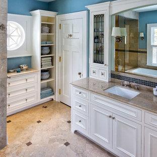 Inredning av ett klassiskt stort brun brunt en-suite badrum, med marmorbänkskiva, beiget golv, luckor med profilerade fronter, vita skåp, ett platsbyggt badkar, en hörndusch, blå kakel, glaskakel, blå väggar, marmorgolv, ett undermonterad handfat och dusch med gångjärnsdörr
