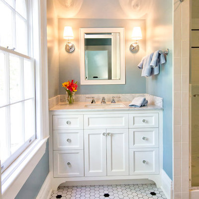 Alcove shower - traditional mosaic tile and white tile porcelain tile and white floor alcove shower idea in New York with recessed-panel cabinets, white cabinets, blue walls, an undermount sink, marble countertops, a hinged shower door and gray countertops
